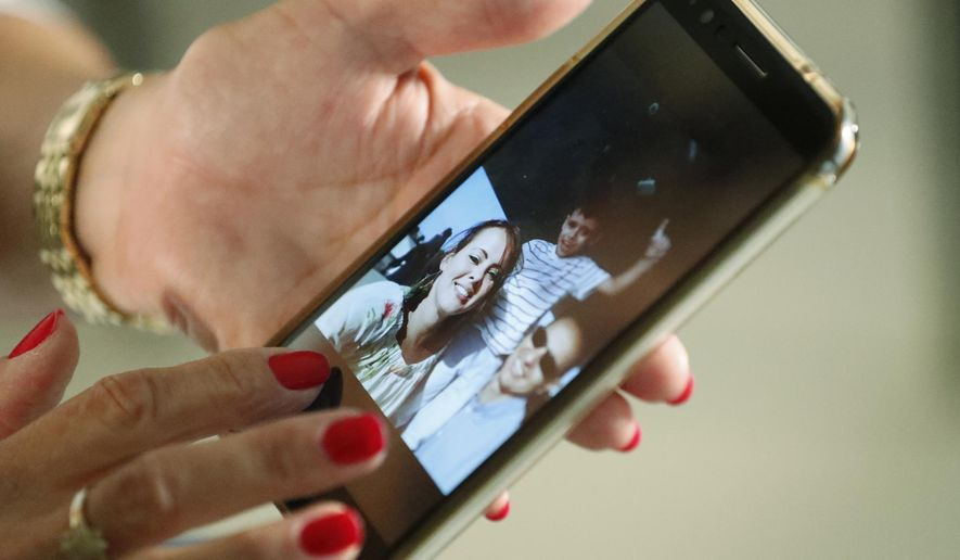 In this June 20, 2019 photo, Mary Sardinas, 60, shows a photo of her son, daughter-in-law and grandson in Cuba as she speaks during an interview with The Associated Press in Miami. Sardinas is among thousands of Cubans living in the United States whose hopes of reuniting with family members have been put on hold since September 2017, when the Trump administration pulled most of its embassy staff out of Cuba in response to a mysterious illness that struck at least two dozen diplomats or their relatives. (AP Photo/Wilfredo Lee)