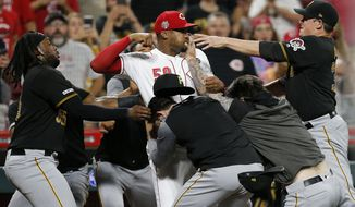 Cincinnati Reds relief pitcher Amir Garrett (50) looks to throw a punch as he is held back by a number of Pittsburgh Pirates players during a brawl in the ninth inning of a baseball game in Cincinnati on Tuesday, July 30, 2019. The Pirates won 11-4. (Sam Greene/The Cincinnati Enquirer via AP)