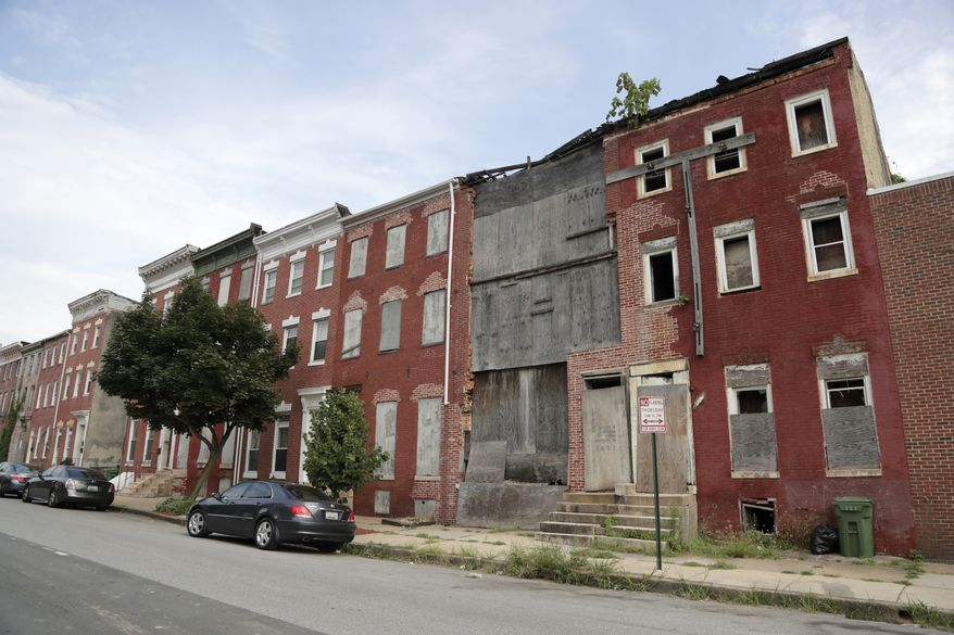 Boards cover the front end of an abandoned row home near the Hollins House, a high-rise building housing seniors and persons with disabilities, which was toured by U.S. Housing and Urban Development Secretary Ben Carson, Wednesday, July 31, 2019, in Baltimore. Carson said the Hollins House, which has 130 one-bedroom units, is an opportunity zone which encourages investment and development in distressed communities. (AP Photo/Julio Cortez)