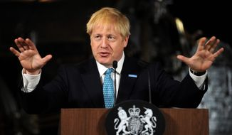 Britain's Prime Minister Boris Johnson gestures during a speech on domestic priorities at the Science and Industry Museum in Manchester, England, Saturday July 27, 2019. Economists have warned that leaving the European bloc without an agreement in under 100-days would disrupt trade to impact on finances and investment. (AP Photo/Rui Vieira)