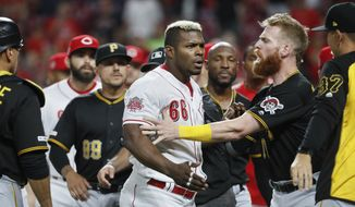 Cincinnati Reds right fielder Yasiel Puig (66) is restrained by Pittsburgh Pirates third baseman Colin Moran, center right, during a bench-clearing in the ninth inning of a baseball game, Tuesday, July 30, 2019, in Cincinnati. (AP Photo/John Minchillo) ** FILE **
