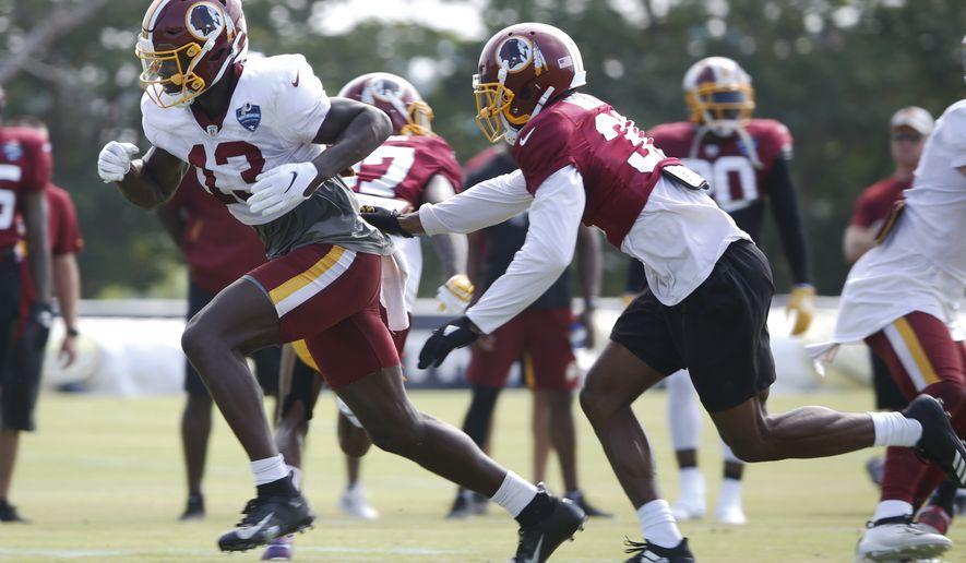 Washington Redskins wide receiver Kelvin Harmon (13) gets past cornerback Fabian Moreau (31) during NFL football training camp in Richmond, Va., Wednesday, July 31, 2019. (AP Photo/Steve Helber) ** FILE **