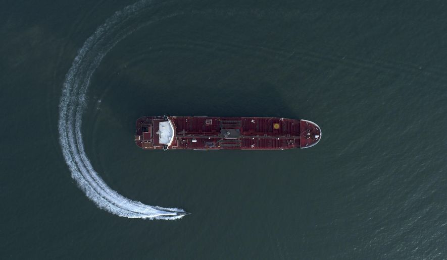 In this Sunday, July 21, 2019, file photo, an aerial view shows a speedboat of Iran's Revolutionary Guard moving around the British-flagged oil tanker Stena Impero, which was seized in the Strait of Hormuz by the Guard, in the Iranian port of Bandar Abbas. (Morteza Akhoondi/Tasnim News Agency via AP) ** FILE **