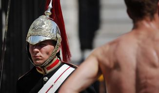 A member of the Queen's Lifeguard marches at Horse guards Parade as temperatures rose far above 30 Celsius (86F) in London, Thursday, July 25, 2019. (AP Photo/Frank Augstein)