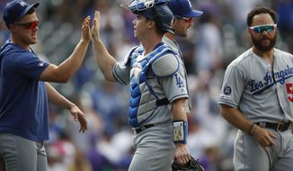 Los Angeles Dodgers' Enrique Hernandez, left, congratulates catcher Will Smith as catcher Russell Martin stands nearby after a baseball game against the Colorado Rockies on Wednesday, July 31, 2019, in Denver. The Dodgers won 5-1. (AP Photo/David Zalubowski)