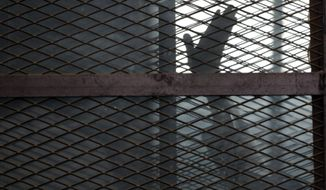 """FILE - In this Aug. 22, 2015 file photo, a Muslim Brotherhood member waves his hand from a defendants cage in a courtroom in Torah prison, southern Cairo, Egypt. Amnesty International said Wednesday, July 31, 2019, that 130 detainees in a notorious Egyptian prison have been on hunger strike for more than six weeks to protest what it calls """"cruel and inhumane detention conditions."""" The detainees are being held at a Cairo prison known as the Scorpion, part of Torah prison, where a number of political figures have been jailed over the course of a sweeping crackdown on dissent in recent years. (AP Photo/Amr Nabil, File)"""