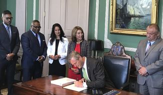 Massachusetts Gov. Charlie Baker signs an overdue $43.3 billion state budget into law, hours before a stopgap spending plan for state government was about to expire at the Statehouse, Wednesday, July 31, 2019, in Boston. (AP Photo/Bob Salsberg)