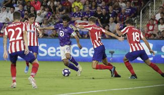 Los Angeles FC forward Carlos Vela (10) tries to moves the ball past Atletico Madrid midfielder Marcos Llorente (14), defender Felipe (18) and defender Mario Hermoso (22) during the first half of the MLS All-Star soccer match Wednesday, July 31, 2019, in Orlando, Fla. (AP Photo/John Raoux)