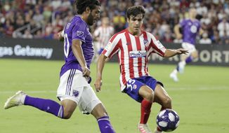 Los Angeles FC forward Carlos Vela, left, tries to get position for a shot against Atletico Madrid defender Manu Sanchez (35) during the first half of the MLS All-Star soccer match Wednesday, July 31, 2019, in Orlando, Fla. (AP Photo/John Raoux)