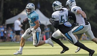 Carolina Panthers' Christian McCaffrey (22) runs as Shaq Green-Thompson (54) and Luke Kuechly pursue during practice at the NFL football team's training camp in Spartanburg, S.C., Monday, July 29, 2019. (AP Photo/Chuck Burton)