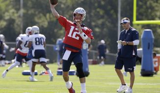 New England Patriots quarterback Tom Brady (12) passes the ball as offensive coordinator Josh McDaniels, right, looks on during an NFL football training camp practice, Thursday, July 25, 2019, in Foxborough, Mass. (AP Photo/Steven Senne)