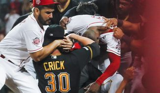Pittsburgh Pirates' Kyle Crick (30) and Cincinnati Reds' Eugenio Suarez, left, and Amir Garrett, center right, are part of a brawl during the ninth inning of a baseball game Tuesday, July 30, 2019, in Cincinnati. (AP Photo/John Minchillo) **FILE**