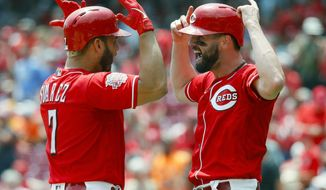 Cincinnati Reds' Eugenio Suarez, left, celebrates with Jesse Winker after hitting a two-run home run off Pittsburgh Pirates starting pitcher Dario Agrazal in the third inning of a baseball game, Wednesday, July 31, 2019, in Cincinnati. (AP Photo/John Minchillo)