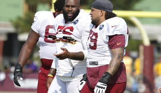 New offensive lineman for the Washington Redskins, Donald Penn (79) talks with offensive tackle Morgan Moses (76) during NFL football training camp in Richmond, Va., Wednesday, July 31, 2019. Penn was signed Wednesday. (AP Photo/Steve Helber)