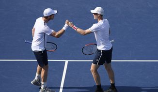 Andy Murray, left, and Jamie Murray, right, both of Britain, bump fists during a doubles match in the Citi Open tennis tournament against Nicolas Mahut and Edouard Roger-Vasselin, both of France, Wednesday, July 31, 2019, in Washington. (AP Photo/Nick Wass)