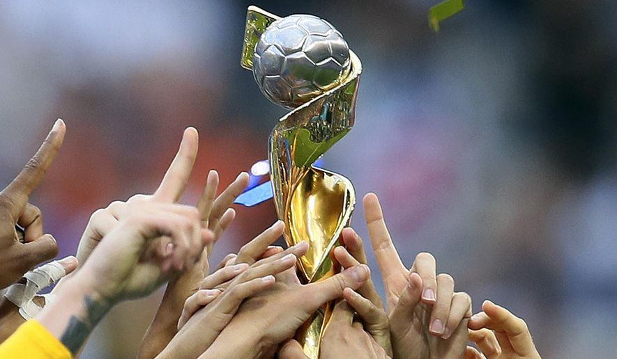 In this July 7, 2019, file photo, U.S. players hold the trophy as they celebrate their victory in the Women's World Cup soccer final in Decines, outside Lyon, France. FIFA's Council has unanimously approved expanding the Women's World Cup from 24 teams to 32 for 2023 and has reopened bidding to host the tournament but made no mention of changing prize money. FIFA said Wednesday, July 31, 2019, the decision was made remotely. (AP Photo/David Vincent, File) **FILE**