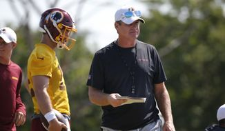 Washington Redskins head coach Jay Gruden, right, gives a play to quarterback Colt McCoy (12) during the Redskins NFL football training camp in Richmond, Va., Thursday, Aug. 1, 2019. (AP Photo/Steve Helber)