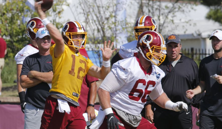 Washington Redskins quarterback Colt McCoy (12) tosses a pass as head coach, Jay Gruden, left, watches during the Redskins NFL football training camp in Richmond, Va., Thursday, Aug. 1, 2019. (AP Photo/Steve Helber) ** FILE **