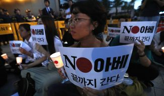 """South Korean protesters stage a rally denouncing the Japanese government's decision on their exports to South Korea in front of the Japanese embassy in Seoul, South Korea, Thursday, Aug. 1, 2019. A 72-year-old South Korean man was in critical condition after setting himself ablaze in downtown Seoul on Thursday, apparently to express his anger toward Japan amid worsening tensions between countries over trade and wartime history, a police official said. The signs read: """"Japanese Prime Minister Shinzo Abe."""" (AP Photo/Ahn Young-joon)"""