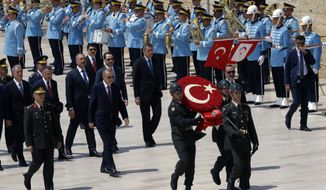 Turkey's President Recep Tayyip Erdogan, centre left, ministers and army commanders follow a guard of honor at the mausoleum of Turkey's founder Mustafa Kemal Ataturk before a meeting of the High Military Council in Ankara, Turkey, Thursday, Aug. 1, 2019. Erdogan joined top commanders for one of the military's most important meetings to promote officers or dismiss others for disciplinary reasons. (AP Photo/Burhan Ozbilici)