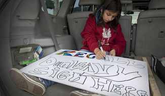 Tianna Minnich, 11, makes a sign for an outpost set up by volunteers from the community to collect signatures for a petition to recall Gov. Mike Dunleavy on Thursday, Aug. 1, 2019, in Ketchikan, Alaska. (Dustin Safranek/Ketchikan Daily News via AP)