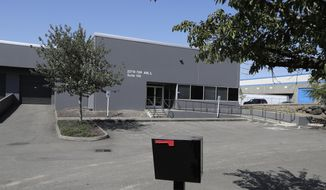 In this Wednesday, July 31, 2019, photo a building that used to house office and storage space for a pawn shop alleged to have been a front for a theft ring stands empty in Kent, Wash. The FBI says the ring sold millions of dollars' worth of stolen goods on Amazon.com in the past six years, and that a pair of Amazon delivery drivers was involved. (AP Photo/Ted S. Warren)