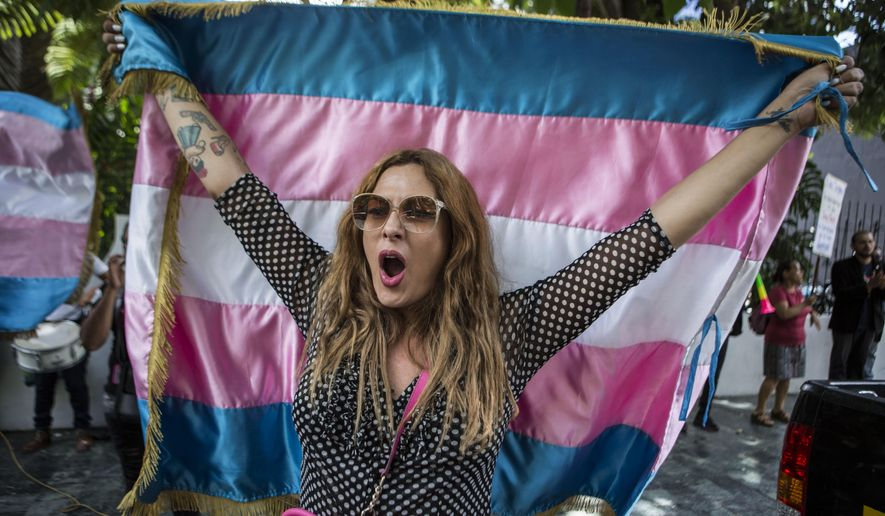 A protester who identifies as transgender waves a transgender flag during a protest against a deal Guatemalan President Jimmy Morales' government signed with Washington that would force Salvadoran and Honduran migrants to request asylum in Guatemala instead of the United States, in Guatemala City, Wednesday, July 31, 2019. Critics of the deal point out that Guatemala has the same problems that are driving Hondurans and Salvadorans to flee their homes: violence, poverty, joblessness and a prolonged drought that has severely hurt farmers. (AP Photo/ Oliver de Ros) **FILE**