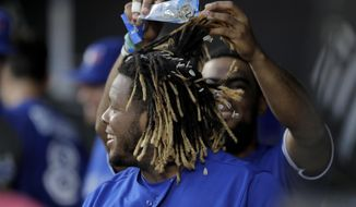 Toronto Blue Jays' Teoscar Hernandez, back, showers Vladimir Guerrero Jr. with sunflower seeds after Guerrero hit a two-run home run off Baltimore Orioles starting pitcher Asher Wojciechowski during the third inning of a baseball game Thursday, Aug. 1, 2019, in Baltimore. (AP Photo/Julio Cortez)