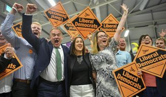 Liberal Democrats' Jane Dodds, centre, celebrates with supporters as she wins the seat in the Brecon and Radnorshire by-election at the Royal Welsh Showground in Llanelwedd, Builth Wells, Wales Friday, Aug. 2, 2019. After a first week in office that saw him booed in Scotland and berated in Belfast, British Prime Minister Boris Johnson was facing his first electoral test on Thursday, a special election that could see his Conservative government's working majority in Parliament cut to just one vote. (Ben Birchall/PA via AP)