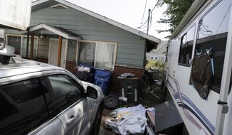 """Vehicles are parked outside the home of Paige A. Thompson, who uses the online handle """"erratic,"""" Wednesday, July 31, 2019, in Seattle. Thompson was taken into custody Monday at her home and has been charged with computer fraud and abuse in connection with hacking data from more than 100 million Capital One credit holders or applicants. (AP Photo/Ted S. Warren)"""