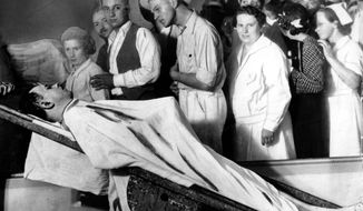 "FILE - In this December 1934 file photo, people view the body of gangster John Dillinger in a Chicago morgue. Two relatives of notorious 1930s gangster John Dillinger who plan to have his remains exhumed say they have ""evidence"" the body buried in an Indianapolis cemetery beneath a gravestone bearing his name may not be him and that FBI agents possibly killed someone else in 1934.  (AP Photo/File)"