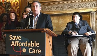 """FILE - In this March 23, 2017, file photo, Wisconsin Sen. Jon Erpenbach speaks at a news conference accompanied by Rep. Jimmy Anderson, right, in Madison, Wis., to warn of """"rationed"""" health care for Wisconsin residents under a Republican health care plan that would replace the Affordable Care Act. The Republican speaker of the Wisconsin Assembly told the paralyzed Democratic state representative, Anderson, in a letter Thursday, Aug. 1, 2019, that he will not grant his request to call in to committee meetings by phone but will pursue other accommodations to appease the lawmaker. Speaker Robin Vos sent Rep. Anderson the letter just hours after The Associated Press contacted every Republican in leadership to see if they agreed with barring Anderson from calling into meetings. (AP Photo/Cara Lombardo, File)"""
