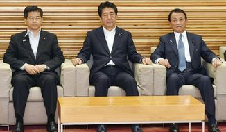 """From left, Japan's Land, Infrastructure and Transport Minister Keiichi Ishii, Prime Minister Shinzo Abe and Finance Minister Taro Aso attend a Cabinet meeting in Tokyo Friday, Aug.  2, 2019. Japan has approved the removal of South Korea from a """"whitelist"""" of countries with preferential trade status, escalating tensions between the neighbors. (Yoshitaka Sugawara/Kyodo News via AP)"""