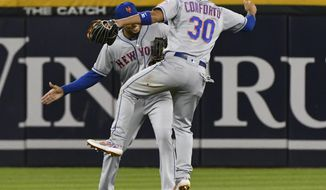 New York Mets outfielders Aaron Altherr, back, and Michael Conforto (30) celebrate at the end of the team's baseball game against the Chicago White Sox, Wednesday, July 31, 2019, in Chicago. The Mets won 4-2. . (AP Photo/Matt Marton)