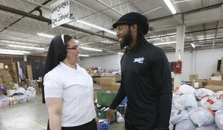 In this June 27, 2019, file photo, Sister Marie Jose De La Rosa, from New Jersey, chats with Washington Redskins cornerback Josh Norman at the Humanitarian Respite Center in McAllen, Texas. Most NFL players don't have the kind of offseason adventures of Josh Norman, who flew with the Blue Angels, visited and donated to an immigrant detention center in Texas and jumped over a bull while running with the bulls in Pamplona, Spain. (Delcia Lopez/The Monitor via AP, File) **FILE**