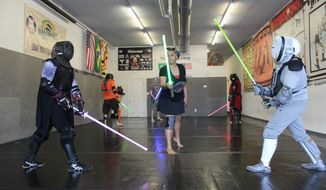 Jessica Newing (center, green saber) prepares to officiate a practice round between Jay Madan (left, purple saber) and Clint Darby (right, yellow saber) at a meeting of The Saber Legion's Maryland chapter in Essex, Md., on June 30, 2019. (Photo by Adam Zielonka / The Washington Times)