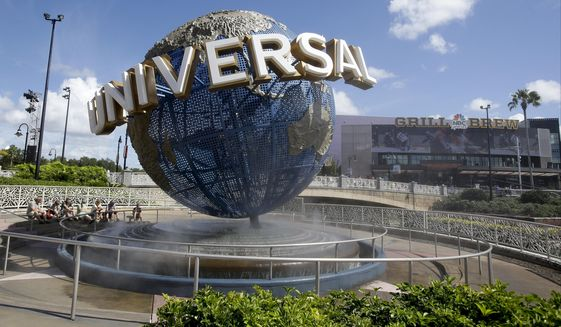 In this Oct. 22, 2015, file photo, park guests relax and cool off with a water mist under the globe at Universal Studios City Walk in Orlando, Fla. (AP Photo/John Raoux, File)