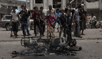 Civilians gather at the site of a deadly attack in Aden, Yemen, Thursday, Aug. 1, 2019. Yemen's rebels have fired a ballistic missile at a military parade in the southern port city of Aden as coordinated suicide bombings targeted a police station in another part of the city. The attacks killed at least 51 people and wounded dozens. (AP Photo/Nariman El-Mofty)