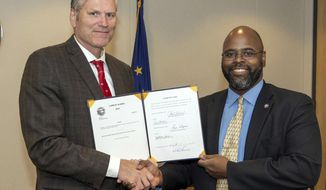 In this Aug. 1, 2019 photo provided by the Governor's Office, Alaska Gov. Mike Dunleavy and state Senator David Wilson pose with signed copies of Senate Bill 25 and Senate Bill 95, sponsored by Wilson, at the governor's office in Juneau, Alaska. The governor's office announced Friday, Aug. 2 that biopsies of skin variations removed from Dunleavy's forehead confirmed a basal cell carcinoma, or a mild form of skin cancer. Sutures from the procedure are seen on the right side of his head. (Austin McDaniel/Office of the Governor via AP)