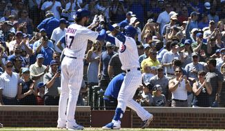 Chicago Cubs' Javier Baez, right, is greeted by Kris Bryant, left, after hitting a two-run home run against the Milwaukee Brewers during the third inning of a baseball game, Friday, Aug. 2, 2019, in Chicago. (AP Photo/David Banks)