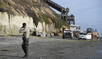 A San Diego County Sheriff's deputy looks on as search and rescue personnel work at the site of a cliff collapse at a popular beach Friday, Aug. 2, 2019, in Encinitas, Calif. At least one person was reportedly killed, and multiple people were injured, when an oceanfront bluff collapsed Friday at Grandview Beach in the Leucadia area of Encinitas, authorities said. (AP Photo/Denis Poroy)