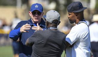 Dallas Cowboys Jerry Jones, left, talks with actor Jamie Foxx, right, at the NFL football team's training camp in Oxnard, Calif., Monday, July 29, 2019. (AP Photo/Michael Owen Baker)
