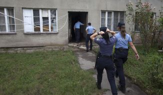 Police enter the house where a suspect killed six people, including a ten-year-old child, before committing suicide, in Zagreb, Croatia, Friday, Aug. 2, 2019. Croatian police identified the killings Friday as domestic violence. (AP Photo/Nikola Solic)