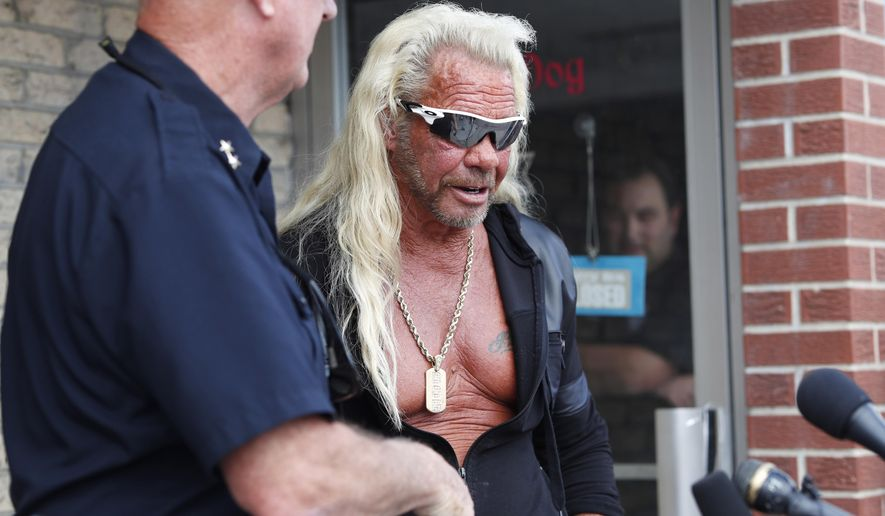 """Duane """"Dog the Bounty Hunter"""" Chapman, right greets John Mackey, chief of police of Edgewater, Colo., during a news conference outside Chapman's storefront that was burglarized Friday, Aug. 2, 2019, in Edgewater, Colo. Police in Colorado said Friday they are investigating a reported burglary of a business owned by """"Dog the Bounty Hunter"""" reality TV star Duane """"Dog"""" Chapman.(AP Photo/David Zalubowski)"""