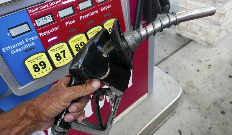 In this June 26, 2019, file photo, a man adds fuel to his vehicle at a gas station in Orlando, Fla. A coalition of states is suing the Trump administration for the second time to block a planned reduction in penalties automakers pay when they fail to meet fuel economy standards. Twelve states and the District of Columbia sued the administration Friday, Aug. 2, 2019, for replacing an Obama-era regulation that imposed a penalty of $14 for every tenth of a mile-per-gallon that an automaker falls below the standards. (AP Photo/John Raoux, File)