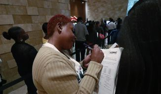 In this June 4, 2019 photo, job applicant Esta Williams, center, uses Tracy Simeton's back to fill out a questionnaire as they wait in line at the Seminole Hard Rock Hotel & Casino Hollywood during a job fair in Hollywood, Fla. On Friday, Aug. 2, the U.S. government issued the July jobs report. (AP Photo/Wilfredo Lee, File)