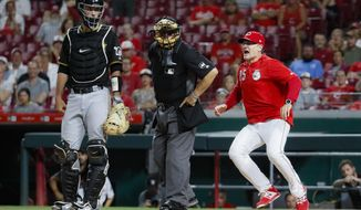 Cincinnati Reds manager David Bell (25) runs up to umpire Larry Vanover, center, to argue a called strike against Yasiel Puig during the ninth inning of a baseball game against the Pittsburgh Pirates on Tuesday, July 30, 2019, in Cincinnati. (AP Photo/John Minchillo)