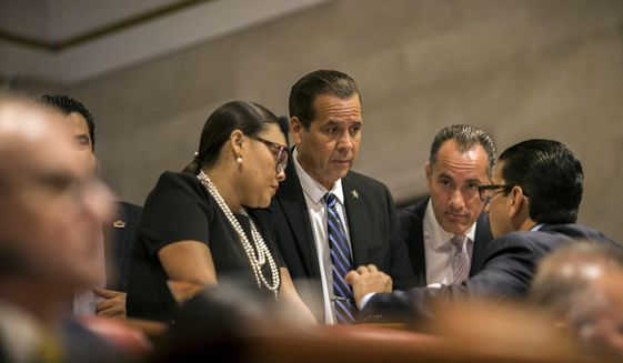 President of the Pedro Pierluisi confirmation hearing, lawmaker Georgie Navarro, center, talks to other representatives before the hearing, at the House of Representatives, in San Juan, Puerto Rico, Friday, August 2, 2019. As Gov. Ricardo Rossello is expected to leave office in a few hours, the Puerto Rican House of Representatives is expected to vote on Pierluisi's confirmation Friday afternoon. If he is rejected, Justice Secretary Wanda Vazquez automatically becomes governor as the next in the order of succession, even though she has said she would unwillingly accept the job. (AP Photo/Dennis M. Rivera Pichardo)
