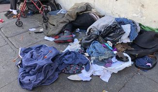 "In this photo taken July 25, 2019, sleeping people, discarded clothes and used needles sit across the street from a staffed ""Pit Stop"" public toilet in the Tenderloin neighborhood in San Francisco. Merchants say the bathrooms have given homeless and other people a private place to go so they don't sully sidewalks as much. (AP Photo/Janie Har)"