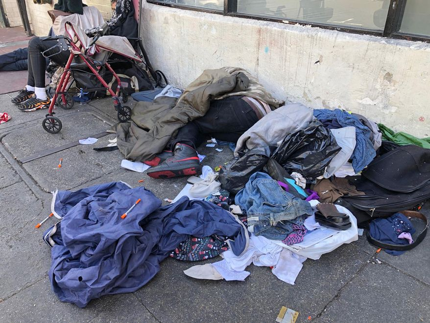 """In this photo taken July 25, 2019, sleeping people, discarded clothes and used needles sit across the street from a staffed """"Pit Stop"""" public toilet in the Tenderloin neighborhood in San Francisco. Merchants say the bathrooms have given homeless and other people a private place to go so they don't sully sidewalks as much. (AP Photo/Janie Har)"""